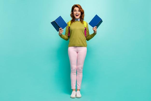Vue sur toute la longueur du corps d'elle, elle séduisante intellectuelle excitée, joyeuse, joyeuse, fille aux cheveux ondulés, lisant un livre s'amusant isolé sur fond de couleur turquoise sarcelle vibrante brillante et brillante