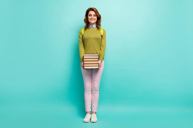 Vue sur toute la longueur du corps d'elle, elle séduisante, intelligente, intelligente, gaie, joyeuse et joyeuse, aux cheveux ondulés, portant une pile de livres le 1er septembre, isolée, brillante, brillante, éclatante, fond de couleur turquoise turquoise