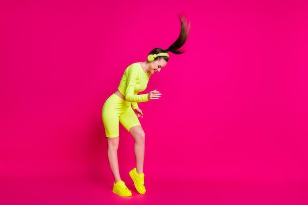Vue sur toute la longueur du corps d'elle, elle séduisante, sportive, mince, fille joyeuse, écoutant de la musique pop rock s'amusant en s'amusant dans une danse de repos isolée, brillante, brillante, éclatante, rose fuchsia, fond de couleur