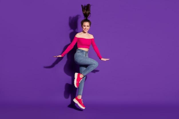 Vue sur toute la longueur du corps d'une fille assez gaie s'amusant à sauter posant isolée sur fond de couleur violet vif