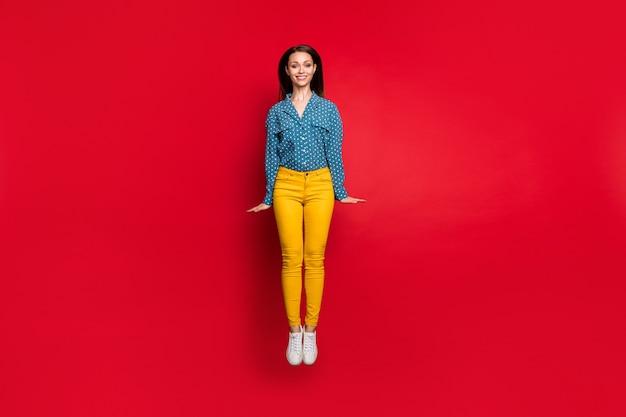 Vue sur toute la longueur du corps d'une fille gaie mince et féminine assez timide sautant en s'amusant isolé sur fond de couleur rouge vif