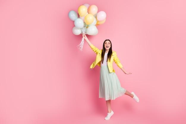 Vue sur toute la longueur du corps d'une fille joyeuse et heureuse tenant dans les mains des balles d'air volent