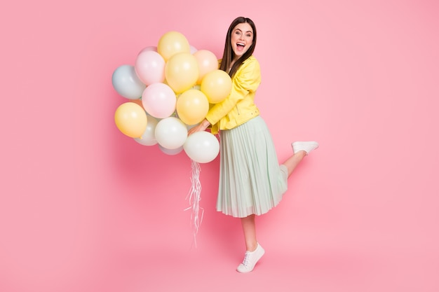 Vue sur toute la longueur du corps d'une fille joyeuse et joyeuse tenant dans les mains des boules d'air excitées