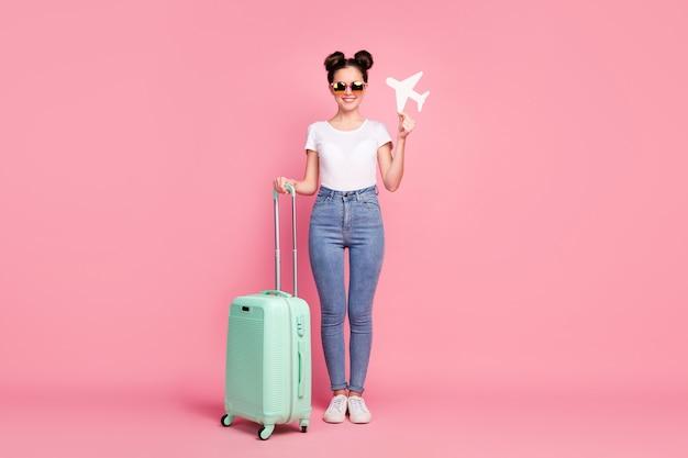 Vue sur toute la longueur du corps d'une fille tenant une tournée de destination de départ d'un avion en papier