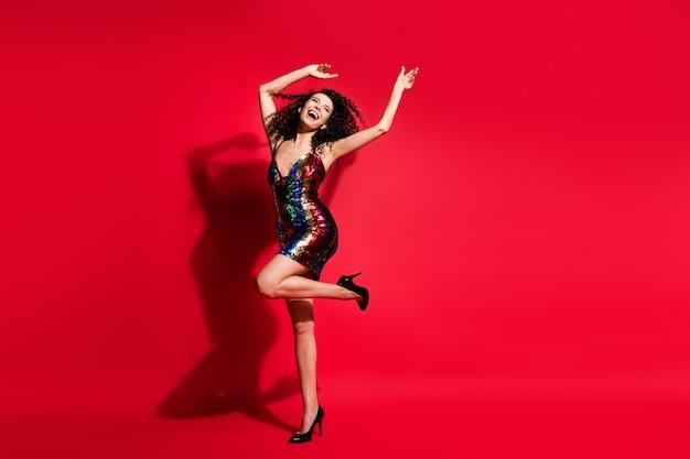 Vue sur toute la longueur du corps d'une jolie fille aux cheveux ondulés chic et gaie s'amusant à danser isolée sur fond de couleur rouge vif