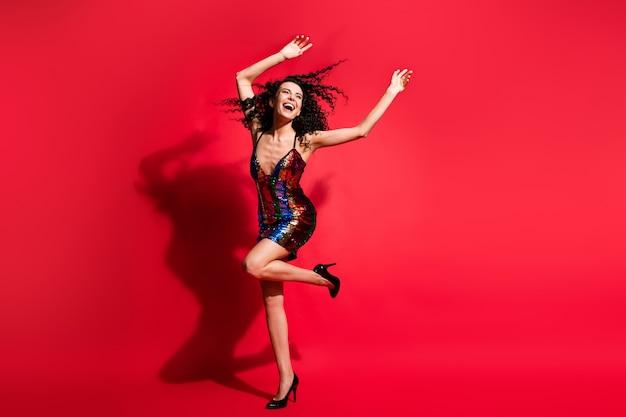 Vue sur toute la longueur du corps d'une jolie fille aux cheveux ondulés gaie et extatique dansant se détendre isolée sur fond de couleur rouge vif