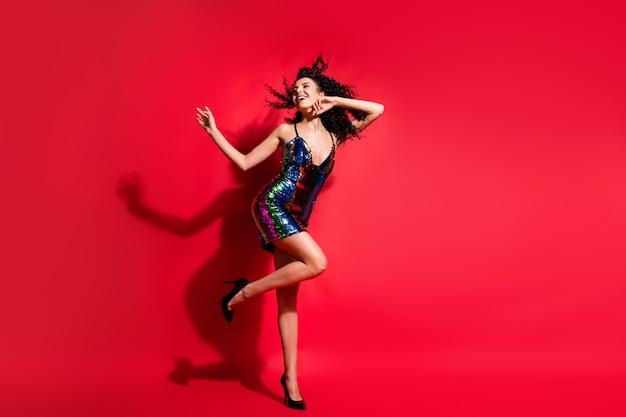 Vue sur toute la longueur du corps d'une jolie fille aux cheveux ondulés rêveuse et gaie dansant en discothèque isolée sur fond de couleur rouge vif