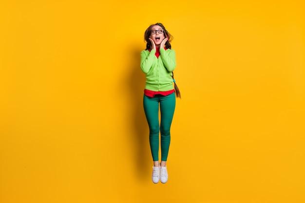 Vue sur toute la longueur du corps d'une jolie fille gaie étonnée et géniale qui saute en s'amusant isolée sur fond de couleur jaune vif