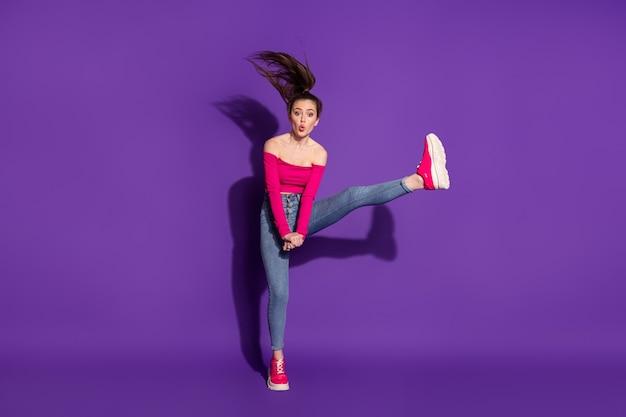 Vue sur toute la longueur du corps d'une jolie fille gaie flexible sautant en s'amusant lèvres moue isolées sur fond de couleur violet vif