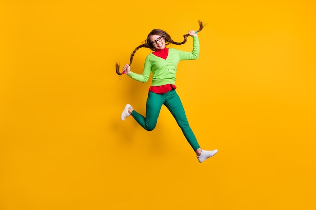Vue sur toute la longueur du corps d'une jolie fille gaie et funky sautant en courant tenant des nattes isolées sur fond de couleur jaune vif