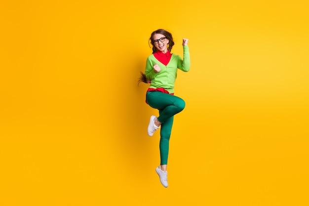 Vue sur toute la longueur du corps d'une jolie fille gaie réussie et funky sautant se réjouissant d'un fond de couleur jaune vif isolé