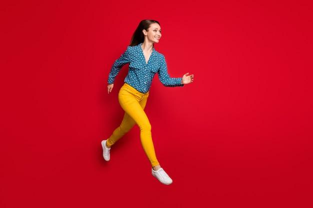 Vue sur toute la longueur du corps d'une jolie fille joyeuse en forme sautant rapidement isolée sur fond de couleur rouge vif