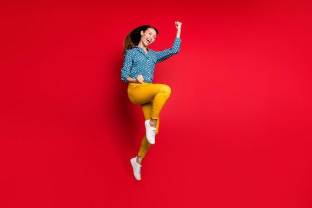 Vue sur toute la longueur du corps d'une jolie fille joyeuse et joyeuse sautant en s'amusant en se réjouissant d'un fond de couleur rouge vif isolé