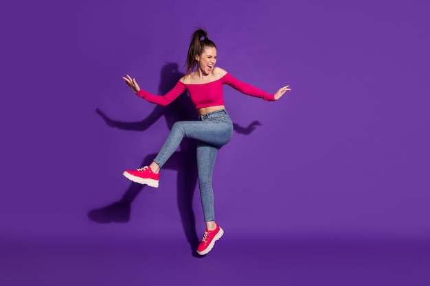 Vue sur toute la longueur du corps d'une jolie fille joyeuse et ravie s'amusant à sauter danse isolée sur fond de couleur violet vif