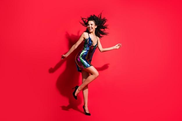 Vue sur toute la longueur du corps d'une jolie fille mince et joyeuse aux cheveux ondulés dansant s'amusant isolée sur fond de couleur rouge vif
