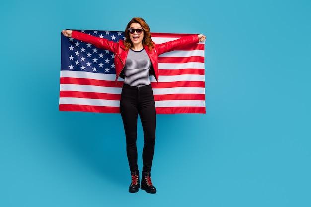 Vue sur toute la longueur du corps d'une jolie jolie fille aux cheveux ondulés, joyeuse et gaie, tenant dans les mains le drapeau des états-unis apprendre la langue anglaise isolée sur un fond de couleur bleu vif et brillant