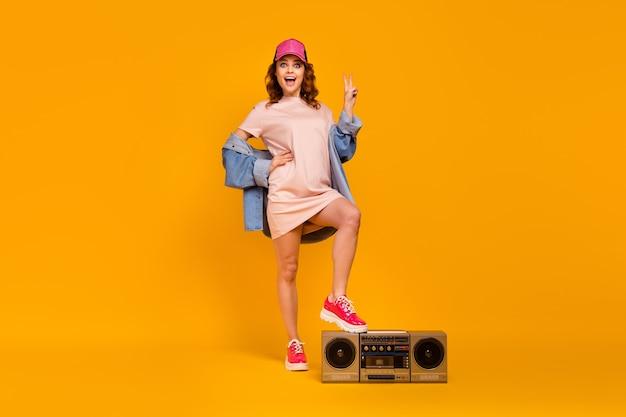 Vue sur toute la longueur du corps d'une jolie jolie fille joyeuse et gaie mettant la jambe sur une boombox montrant le signe v s'amusant isolé sur un fond de couleur jaune vif éclatant