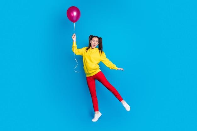 Vue sur toute la longueur du corps d'une jolie jolie jolie ravie heureuse gaie joyeuse fille sautant tenant dans la main un ballon d'air s'amusant des loisirs isolés brillant vif éclat fond de couleur bleu vif
