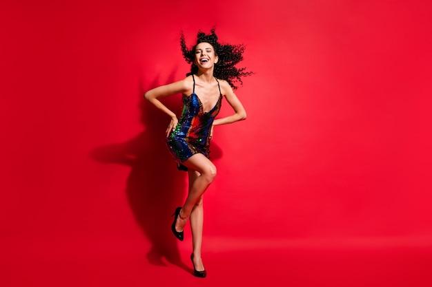 Vue sur toute la longueur du corps d'une magnifique fille joyeuse et joyeuse aux cheveux ondulés dansant appréciant isolée sur fond de couleur rouge vif