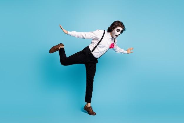 Vue sur toute la longueur du corps de son beau monsieur effrayant comique funky s'amusant à sauter en tombant sur le thème des zombies isolé sur fond de couleur bleu vif brillant éclatant