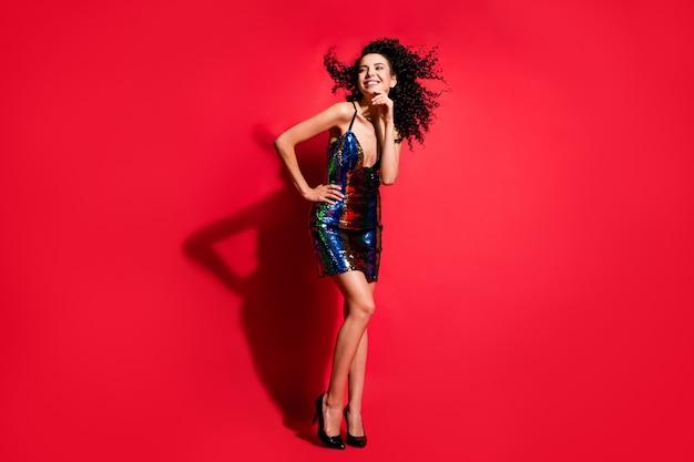 Vue sur toute la longueur du corps d'une superbe fille aux cheveux ondulés chic et joyeux s'amusant en s'amusant isolé sur fond de couleur rouge vif
