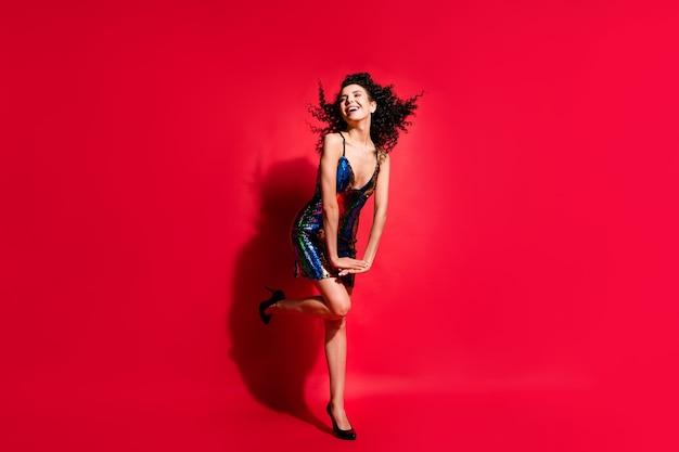 Vue sur toute la longueur du corps d'une superbe fille aux cheveux ondulés gaie s'amusant à danser isolée sur fond de couleur rouge vif