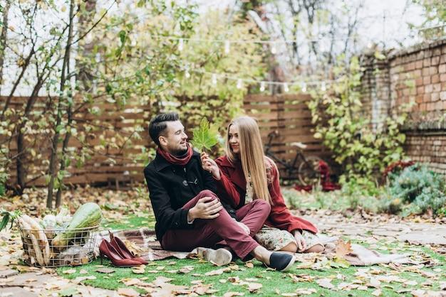 Vue sur toute la longueur du couple amoureux de la feuille d'érable en train de pique-niquer dans le parc d'automne et de se regarder tout en profitant d'une belle journée