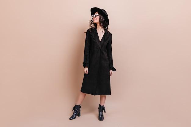 Vue sur toute la longueur de la femme brune rêveuse en lunettes de soleil et manteau. superbe femme élégante au chapeau debout sur fond beige.