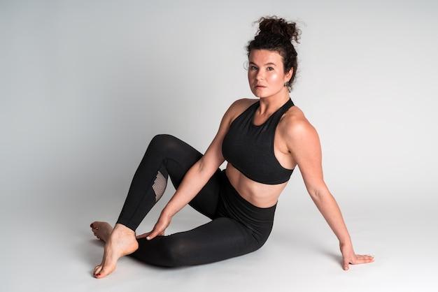 Vue sur toute la longueur de la femme fitness en tenue de sport noire assise au sol et se relaxant tout en posant devant la caméra. studio intérieur tourné isolé sur fond blanc