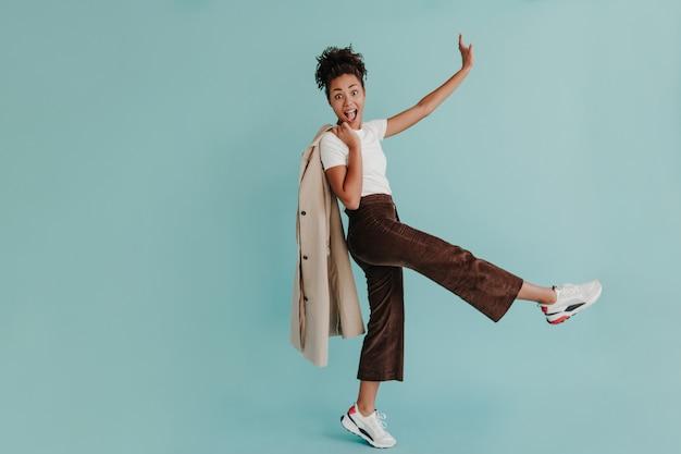 Vue sur toute la longueur d'une femme merveilleuse dansant sur un mur turquoise