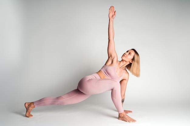 Vue sur toute la longueur de la femme de yoga en tenue de sport pratiquant le yoga dans une salle de classe lumineuse avec un mur blanc en arrière-plan. concept de sport et de loisirs