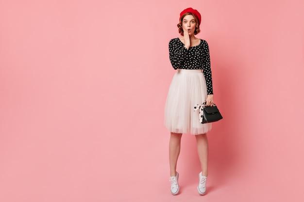 Vue sur toute la longueur de la fille surprise en jupe blanche. photo de studio d'une femme française étonnée en béret élégant.