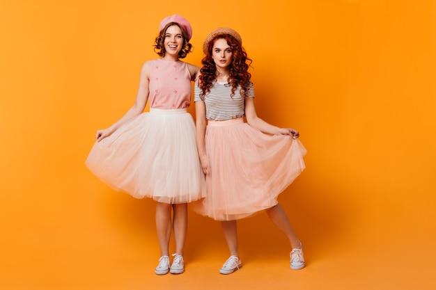 Vue sur toute la longueur des filles jouant avec des jupes. photo de studio d'amis féminins glamour debout sur fond jaune.