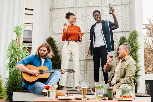 Vue sur toute la longueur d'un groupe d'amis dansant lors d'une fête en plein air sur le toit, avec un jeune homme jouant de la guitare au premier plan, espace pour copie