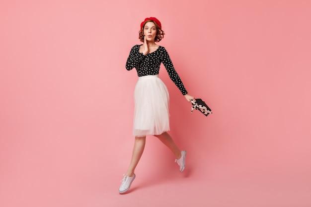 Vue sur toute la longueur de la jolie fille française avec sac à main. photo de studio de jeune femme glamour posant sur fond rose.
