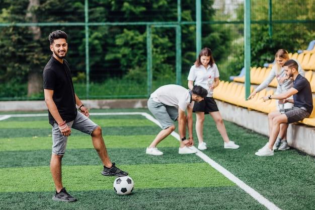 Vue sur toute la longueur d'un joueur de football afro-américain athlétique restant avec une balle sur un terrain vert