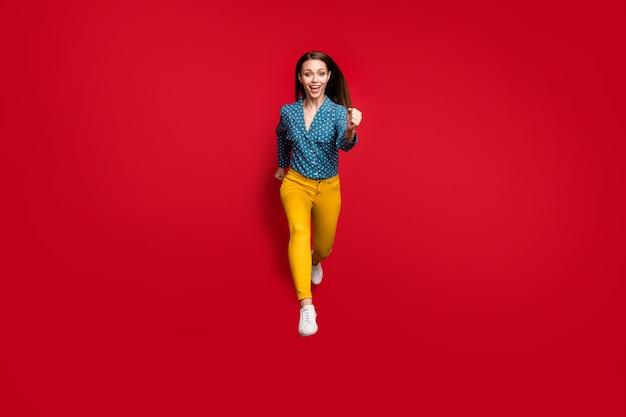 Vue sur toute la longueur de la taille du corps d'une belle fille gaie sportive motivée et attrayante sautant en cours d'exécution sur fond de couleur rouge vif isolé