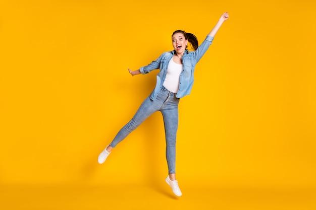 Vue sur toute la longueur de la taille du corps d'elle, elle attrayante, ravissante, joyeuse, joyeuse, joyeuse, amusante, amusante, sautant, tenant un parapluie invisible, prévision isolée, brillante, éclat vif, fond de couleur jaune vif