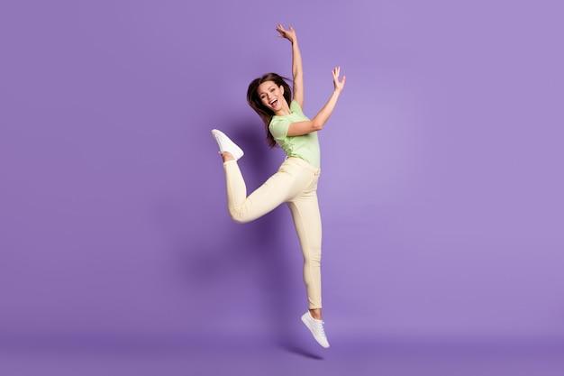 Vue sur toute la longueur de la taille du corps d'elle, elle est belle et attirante, mince, flexible, joyeuse, joyeuse, sautant en s'amusant chorégraphie d'aérobic isolée, brillant vif, brillant, fond de couleur violet lilas vibrant