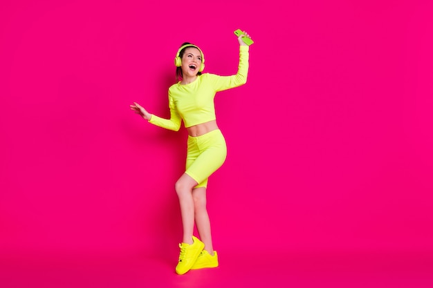 Vue sur toute la longueur de la taille du corps d'elle, elle est belle et attirante, mince, joyeuse, joyeuse, écoutant de la musique différente, dansant, s'amusant, reste isolée, brillante, éclat vif, fond de couleur rose fuchsia vibrant