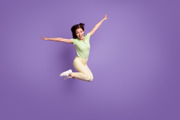 Vue sur toute la longueur de la taille du corps d'elle, elle est belle et attrayante, mince, mince, insouciante, funky, joyeuse, joyeuse, sautant en s'amusant à voler isolé, lumineux, brillant, brillant, fond de couleur violet lilas vibrant