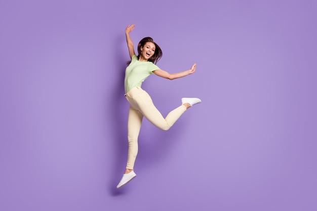 Vue sur toute la longueur de la taille du corps d'elle, elle est belle fille gaie, sportive et flexible, sautant en s'amusant chorégraphie moderne isolée, brillant, éclat vif, fond de couleur violet lilas vibrant