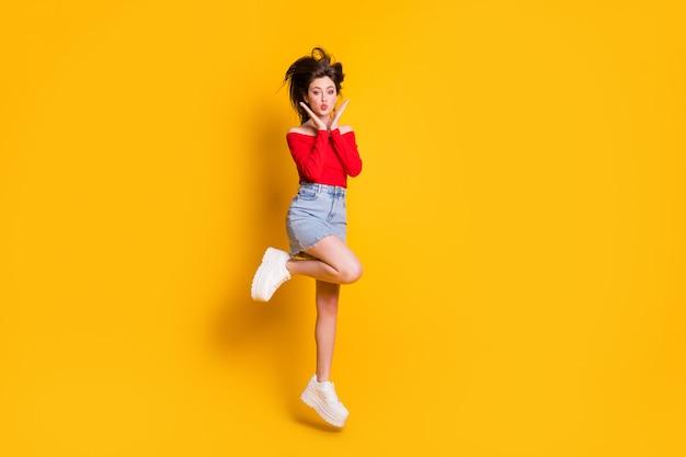 Vue sur toute la longueur de la taille du corps d'elle, elle est belle, jolie, jolie, adorable, gaie, mince, maigre, géniale, fille sautant en s'amusant, lèvres moue isolées, brillant, éclat vif, fond de couleur jaune vif