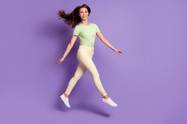 Vue sur toute la longueur de la taille du corps d'elle, elle est belle, jolie, jolie, gaie, joyeuse, gaie, svelte, sautant, s'amusant, isolée, brillante, éclatante, fond de couleur violet lilas vibrant