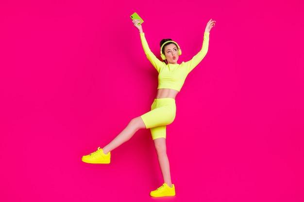 Vue sur toute la longueur de la taille du corps d'elle, elle est belle et séduisante, fille gaie et funky, écoutant de la musique pop, dansant, s'amusant, lèvres moue isolées, brillant, éclat vif, fond de couleur rose fuchsia vibrant