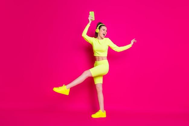Vue sur toute la longueur de la taille du corps d'elle, elle est belle et séduisante, mince, gaie, joyeuse, joyeuse, fille heureuse, écoutant de la musique pop, dansant, reste froid isolé, brillant, brillant, éclatant, fond de couleur rose fuchsia