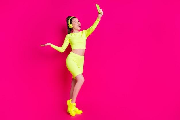 Vue sur toute la longueur de la taille du corps d'elle, elle est belle, séduisante, mince, joyeuse, joyeuse, fille heureuse, écoutant de la musique, prenant du temps libre pour selfie, isolée, brillante, brillante, éclatante, fond de couleur rose fuchsia