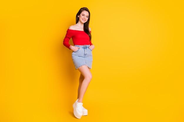 Vue sur toute la longueur de la taille du corps d'elle, elle est jolie, jolie, jolie, mince, joyeuse, aux cheveux bruns, posant vêtue d'un haut rouge isolé sur un fond de couleur jaune vif et brillant