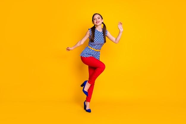 Vue sur toute la longueur de la taille du corps d'elle, elle est jolie, jolie, à la mode, élégante, ajustée, gaie, gaie, fille joyeuse, dansant, s'amusant, déplaçant isolé, brillant, brillant, éclatant, fond de couleur jaune vif