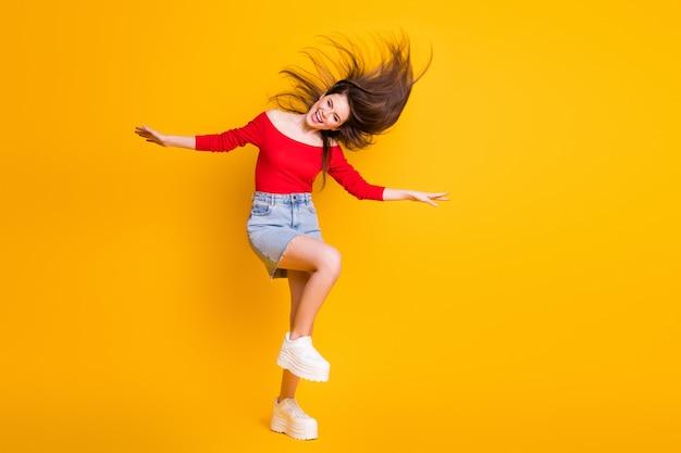 Vue sur toute la longueur de la taille du corps d'elle, elle est jolie, séduisante, gaie, joyeuse, heureuse, danse, s'amusant, discothèque, vie nocturne, isolée, brillante, éclat vif, fond de couleur jaune vif